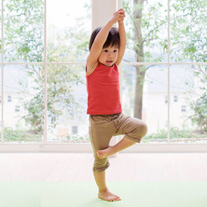Young child practicing yoga tree pose